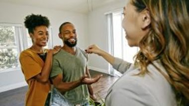 real-estate-agent-handing-clients-a-key-GettyImages-1006937990-1300w-867h
