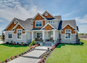 Large stone and shingle house with a large front yard